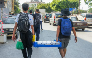 backs of men pictured carrying a pallet of meals to be given out in beirut