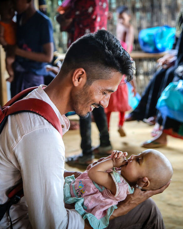 A father holds his baby and smiles at her
