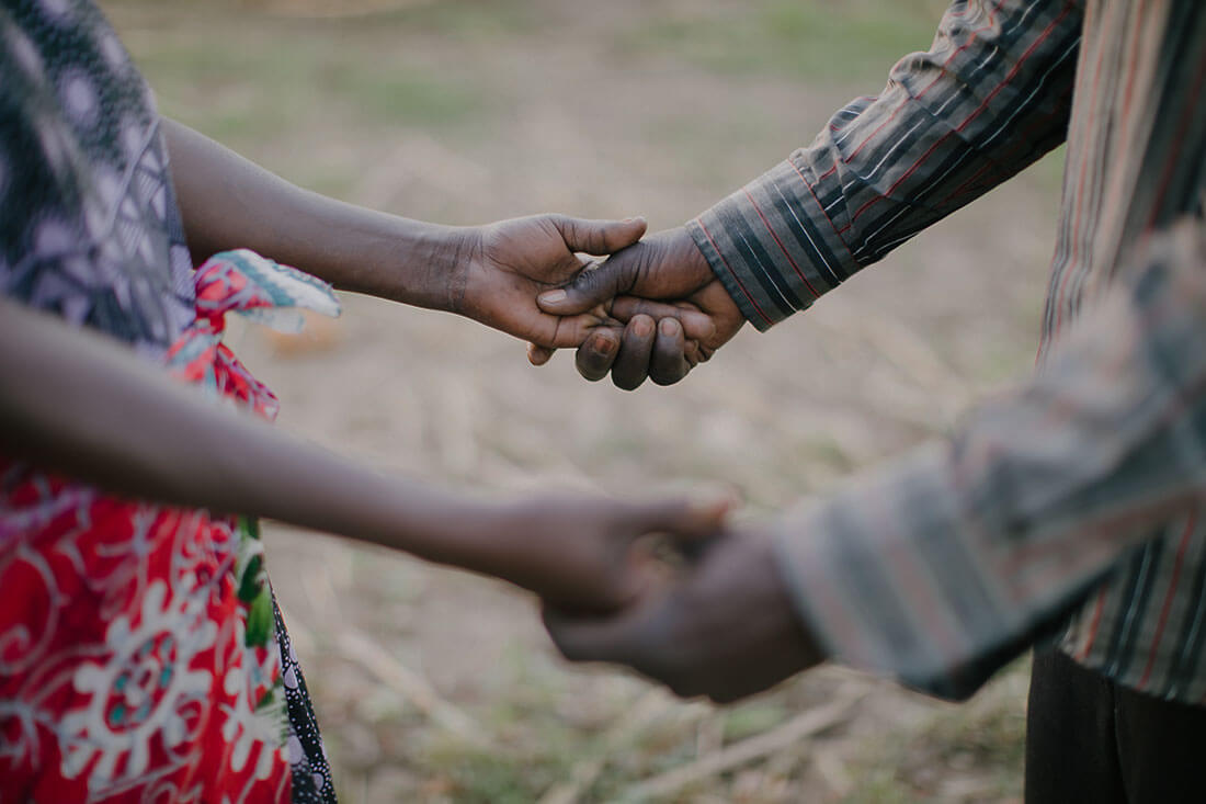 A close up of a Black couple holding hands