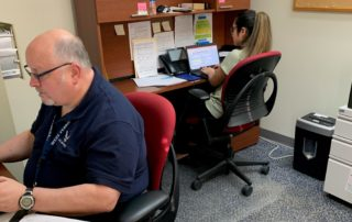 man and woman sit at desks completing paper work
